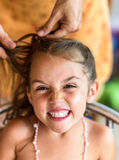 Mother is making of braids on little daughter's head. Stock Photos