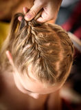 Mother is making of braids on little daughter's head. Royalty Free Stock Photography