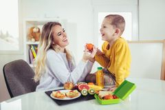 Mother making breakfast for her children. In the morning and a snack for school Royalty Free Stock Photography