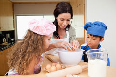 Mother making cookies with her kids. Mother making cookies together with her kids Royalty Free Stock Photo
