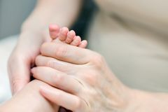 Mother making feet massage for infant baby. Parent care about kid. Children health car and disease prevention.  Stock Image
