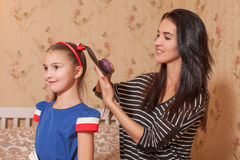 Mother making hairstyle  to her daughter Stock Photo