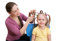 A mother is making her little daughter a beautiful hairstyle Stock Image