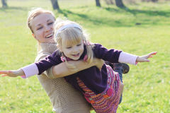 Mother making little daughter fly Stock Photography