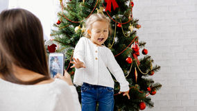 Mother making photo with smart phone of her little daughter near christmas tree. Baby girl funny posing and playing the ape for photography Stock Photography