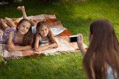 Mother making photo of two girls lying on grass Royalty Free Stock Image