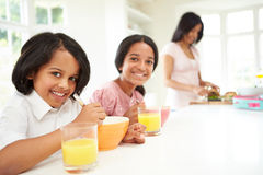 Mother Making School Packed Lunches For Children. Who Are Smiling To Camera Stock Image