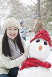 Mother making snowman in park in winter Stock Image