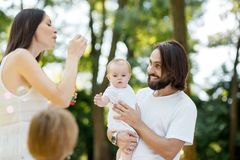 Mother making soap bubbles outdoor. Father with daughter in the arms and son next to him are looking at mom and enjoying royalty free stock images