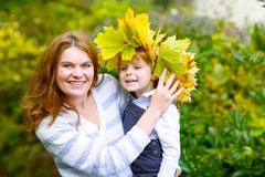 Mother with maple leaf wreath holding little toddler boy in autu. Young mother with a maple leaf wreath holding little toddler kid boy in autumn park. Happy Stock Images