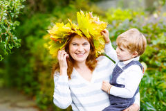 Mother with maple leaf wreath holding little toddler boy in autu. Young mother with a maple leaf wreath holding little toddler kid boy in autumn park. Happy Royalty Free Stock Image