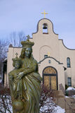 Mother Mary and Baby Jesus With Church in Background Stock Photos