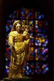 Mother Mary and Jesus statue. Enlightened statue with virgin mother Mary and baby Jesus with blurred stained glass background Royalty Free Stock Image