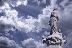 Mother Mary Surrounded by Angels with Light from Heaven. With fluffy clouds in a blue sky Stock Photo
