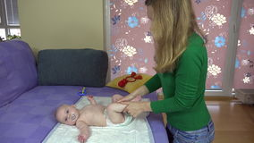 Mother massage her little baby daughter legs on bed stock footage