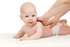 Mother massaging her baby boy. Baby boy lying on towel Stock Photography