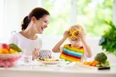Mother matande barn Mamman matar ungegr?nsaker arkivfoton