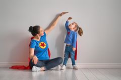 Mother is measuring growth of child. Daughter near empty wall. Girl in superhero costume Stock Images