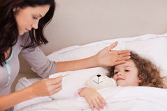 Mother measuring her daughters temperature Stock Photography