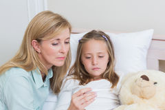 Mother measuring her daughters temperature Stock Image