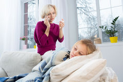 Mother measuring temperature of her child and calling doctor. stock photography