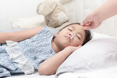 Mother measuring temperature of her ill kid. Sick child with high fever laying in bed and mother holding thermometer Stock Photo