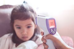 Mother measuring temperature her sick asian little child girl stock images