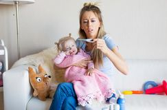Mother measuring temperature of her sick crying baby. Mother sitting at home with sick children Stock Photography