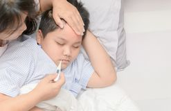 Mother measuring temperature of ill kid royalty free stock images