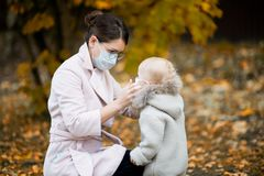 Mother in a medical face mask adjusts the medical mask to her little daughter