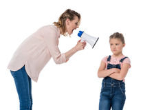 Mother with megaphone screaming at little daughter standing with crossed arms Royalty Free Stock Images