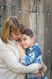 Mother and Mixed Race Son Hug Near Fence Stock Photo