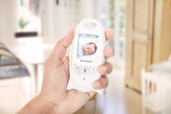 Mother mnitoring sleeping baby through baby monitor. A Mother mnitoring sleeping baby through baby monitor Stock Photo
