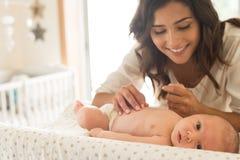 Mother moisturizing baby Stock Photography