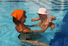 Mother mom with baby in the pool. Mother mom learning baby how to swim Stock Image
