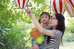 Mother mom embrace hug her daughter smile laugh have fun enjoy free time in summer park happy child childhood play with balloon stock image