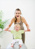 Mother mother holding baby sitting on fitness ball. In gym Royalty Free Stock Photo