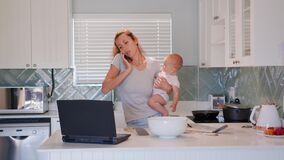 Mother multi-tasking, holding baby infant and using computer laptop at home. Candid authentic and real life mom working