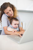 Mother multi tasking at home Royalty Free Stock Image