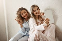 Mother is my best friend forever. Charming caucasian daughter in pyjamas taking selfie with mom using digital tablet. Smiling at screen, spending leisure in Royalty Free Stock Photos