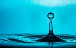 Mother Natures Crystal Clear Pure Blue Water Drop. This picture is of a classic single pure crystal clear water drop that has dropped onto the surface of a pool stock image