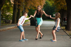 Mother with naughty son adn daughter on a walk in park. On summer evening stock photography