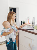 Mother navigating the internet with baby in arms Stock Photography