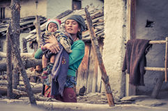 Mother in Nepal. Dolpo, Nepal - circa May 2012: Native woman with grey headcloth wears green sweatshirt and holds her child covered in violet scarf and with red Royalty Free Stock Photography