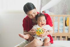 Mother and new born baby play a toy and fun together royalty free stock images