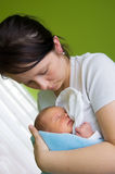 Mother with newborn. Two week baby sleeping on mother's arms stock photo