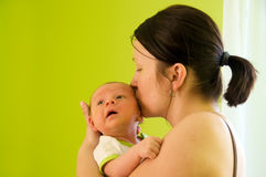 Mother and newborn. Four week baby in mother's arms. Mother kisses her baby in temple Stock Photos