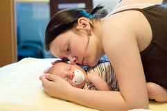 Mother with newborn. Baby sleeping in mother's arms on yellow blanket stock images