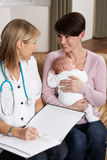 Mother With Newborn Baby. Talking With Health Visitor At Home Royalty Free Stock Photos
