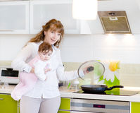 Mother with a newborn baby cook food in the kitche Royalty Free Stock Photos